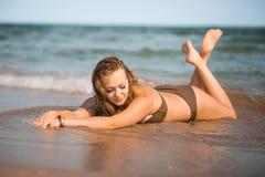 La fille bronzée sexy dans un maillot de bain se trouve sur le bord de la mer Photographie stock