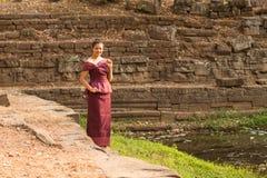 La fille cambodgienne dans la robe de Khmer se tient prêt une piscine de l'eau à Angkor Thom photographie stock libre de droits