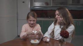 La fille casse un oeuf de poulet dans la cuvette se reposant à la table dans la cuisine avec sa soeur plus âgée banque de vidéos