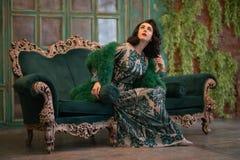 La fille caucasienne élégante dans de longues paillettes luxueuses lacent la robe avec un boa pelucheux vert dans des ses mains p image libre de droits