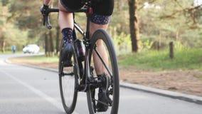La fille caucasienne adapt?e de triathlete monte un v?lo en parc ?troitement vers le haut de p?daler Les muscles de jambe se ferm banque de vidéos