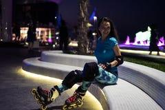 La fille caucasienne apprécie le patinage de rouleau à la ville de nuit avec des lumières dans le bokeh Photographie stock libre de droits