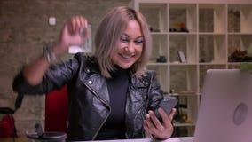 La fille caucasienne blonde excitée montre la vue de victoire avec sa main tout en regardant l'écran à son téléphone, énergique clips vidéos