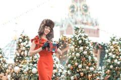 La fille caucasienne dans une robe rouge dans le chapeau russe avec des oreille-ailerons joue sur un accordéon pendant l'hiver da image stock