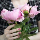 La fille caucasienne tient le bouquet rose de pivoines devant elle Image libre de droits