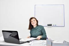 La fille châtain devant l'écran d'ordinateur portable parle heureusement sur Skype Le concept de l'enseignement à distance image stock