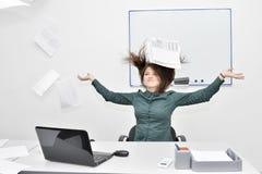 La fille châtain heureuse dans le bureau derrière l'ordinateur portable a jeté des papiers et des documents photos libres de droits