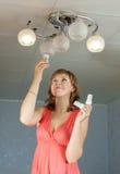 La fille change l'ampoule image stock
