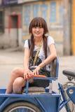 La fille chinoise mignonne s'asseyent sur le tricycle de het, Zhuozhou, province de Hebei, Chine Image stock