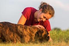 La fille choie son chien de boxeur Images libres de droits