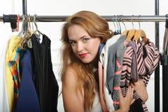 La fille choisit des choses à un magasin d'habillement images stock