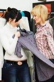 La fille choisit des vêtements dans une boutique Images libres de droits
