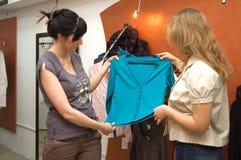 La fille choisit des vêtements sur le marché Photo libre de droits