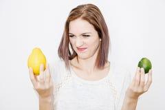 La fille choisit entre le citron et la chaux Chaux ou citron Photo libre de droits