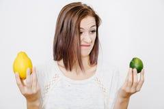 La fille choisit entre le citron et la chaux Chaux ou citron Photos libres de droits