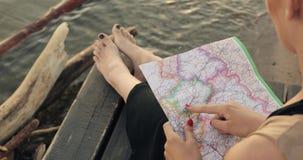La fille choisit l'itinéraire de voyage sur la carte se reposant à la jetée sur la plage de mer banque de vidéos