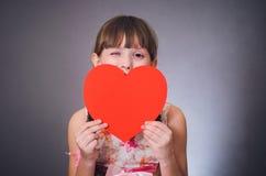 La fille cligne de l'oeil un oeil et ferme un coeur de bouche Image stock