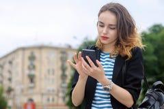La fille communique sur un téléphone portable et un sourire photos libres de droits