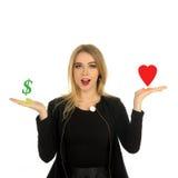 La fille compare l'amour et l'argent Photographie stock libre de droits