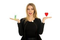 La fille compare l'amour et l'argent Photos libres de droits