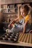 La fille concentrée mignonne mettant la pâtisserie dans la cuisson sonne Photos stock
