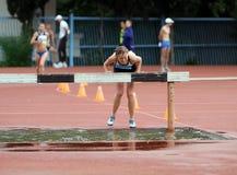 La fille concurrencent dans la course d'obstacles de 3.000 mètres Image stock