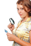 La fille considère un par la carte de crédit par une loupe Photo stock