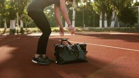 La fille convenable de brune attrayante est venue à une forme physique, stade de sport dehors Met des sports noirs mettent en sac banque de vidéos