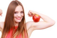 La fille convenable de femme tient le fruit de pomme sur son bras de biceps Images libres de droits