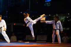 La fille coréenne de Taekwondo sautent des coups de pied cassant le panneau Photographie stock libre de droits