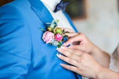La fille corrige le boutonniere de marié de jeune mariée faire de la publicité de fleurs Weddi Images stock