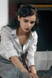 La fille coud des vêtements Elle est habillée dans une chemise blanche Photographie stock
