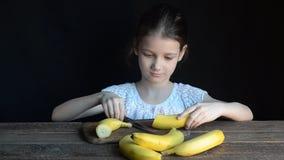 La fille a coupé la banane sur une planche à découper banque de vidéos