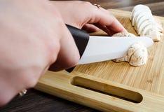 La fille coupe des champignons de couche Photo stock