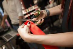 La fille coupe le ruban rouge avec des ciseaux Événement d'ouverture Fermez-vous vers le haut de la vue photos stock
