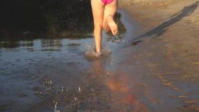 La fille court nu-pieds le long du rivage et du jeu dans l'eau sur la plage au coucher du soleil Éclabousse de la mouche de l'eau banque de vidéos