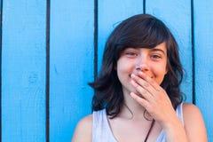 La fille couvre sa bouche de sa main, sur le fond des murs en bois bleus Photo stock
