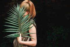 La fille couvre son visage de branche de fougère Photographie stock
