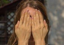 La fille couvre son visage de ses mains image stock