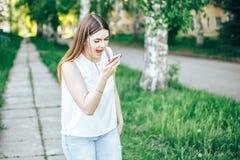 la fille crie au téléphone portable en parc images libres de droits
