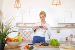 La fille culinaire tient le smartphone dans des mains et prend la photo du veget Photographie stock libre de droits