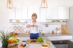 La fille culinaire tient le smartphone dans des mains et prend la photo du veget Images libres de droits