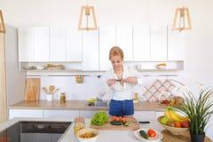 La fille culinaire tient le smartphone dans des mains et prend la photo du veget Photo stock