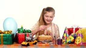 La fille décore un gâteau avec des bougies, se reposant au clips vidéos