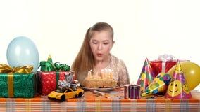 La fille décore un gâteau avec des bougies, se reposant au banque de vidéos