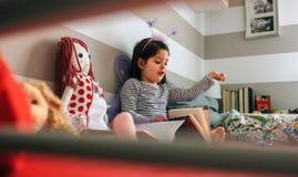 La fille a déguisé lire un livre à sa poupée Photographie stock