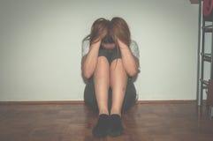 La fille déprimée et seule maltraitée en tant que jeunes seul se reposant dans sa chambre sur le sentiment de plancher malheureux Photographie stock