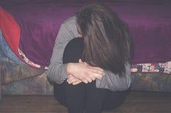 La fille déprimée et seule maltraitée en tant que jeunes seul se reposant dans son sentiment de chambre malheureux et inquiétude  photographie stock