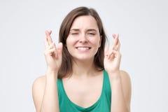 La fille désireuse de gagner la concurrence, maintient des doigts croisés comme attentes des résultats images stock