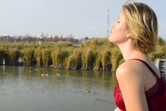 La fille détend à la garde de pilier près du lac Fille sur le fond d'un étang avec des canards La blonde détend Images libres de droits